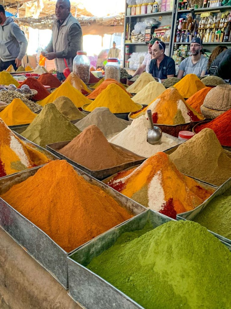 piles of colorful spices at a market in Morocco