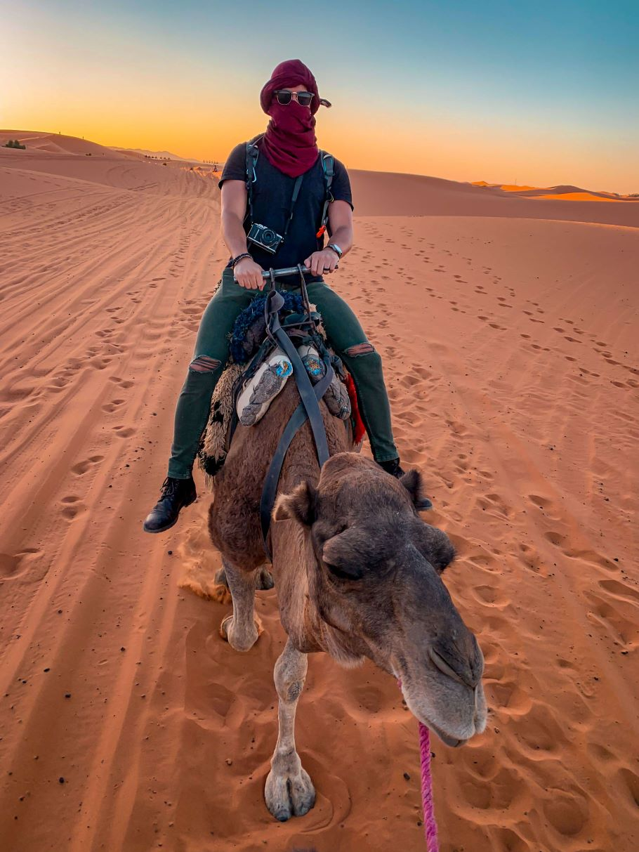 Camel riding at sunset at Erg Chebbi sand dunes in the Sahara desert, Morocco