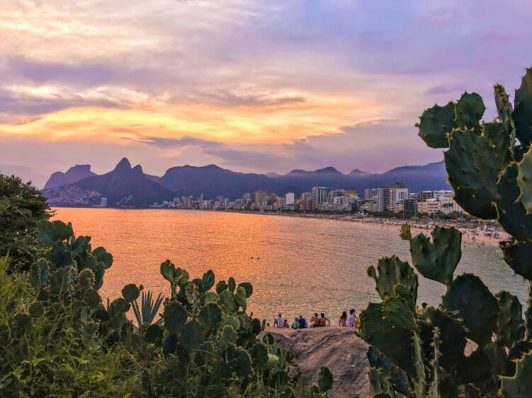 The sunset view from Arpoador cliff over Ipanema beach and the Two Brothers Mountains (Morro Dois Irmaos)