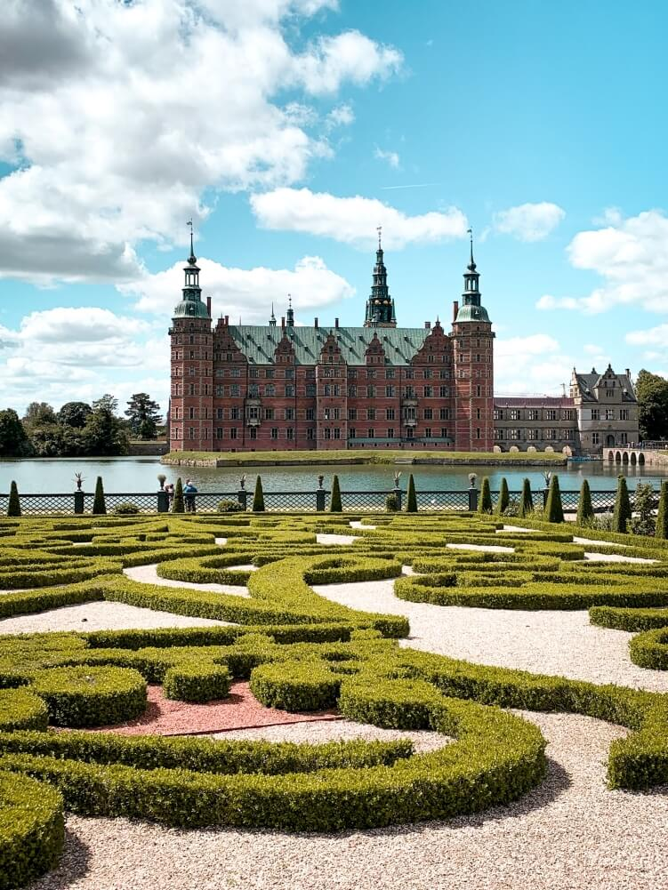 Renaissance-style Frederiksborg Castle with perfectly trimmed hedges and Castle Lake in Hillerod