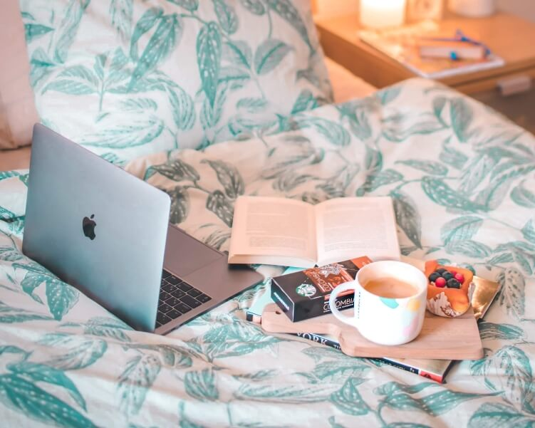 A laptop and a cup of coffee in bed - the perfect cozy setting to watch sustainable travel documentaries during COVID-19 self-isolation