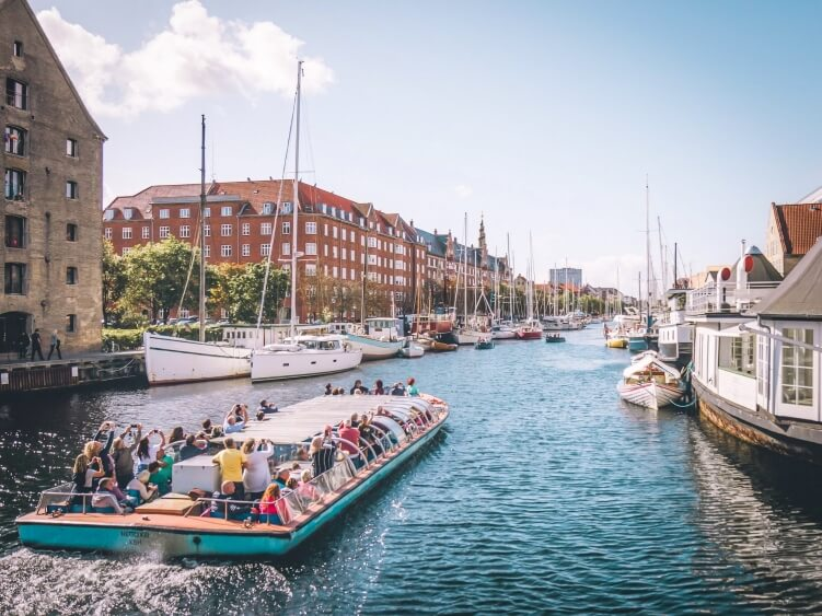 Tourists on a Copenhagen canal tour boat sailing through the Christianshavn neighborhood, one of the best Copenhagen bucket list activities
