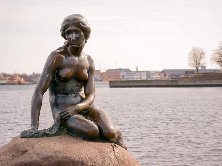 The bronze statue of the Little Mermaid - one of the most popular tourist attractions in Copenhagen and a place you should add to your Copenhagen bucket list