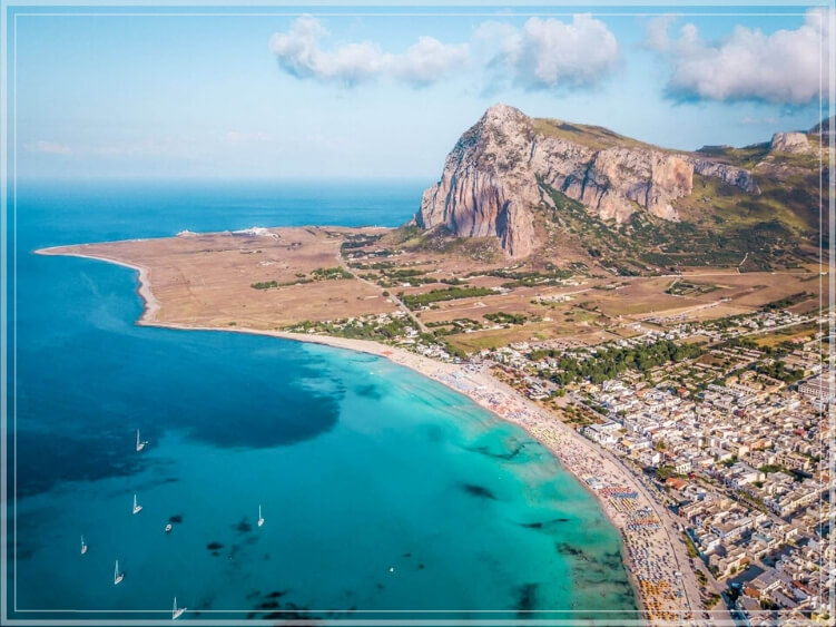 A bird's eye view of the beautiful beach with white sand and clear water at the town of San Vito Lo Capo, Sicily