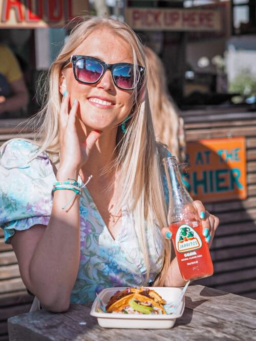 a girl enjoying tacos at Torvehallerne street food market in Copenhagen