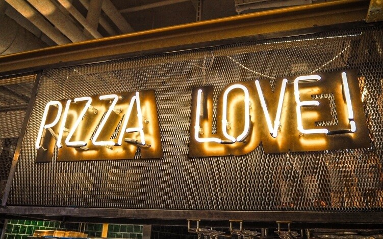 "A neon sign stating ""Pizza Love"" in Tivoli Food Hall, one of the best markets for street food in Copenhagen"