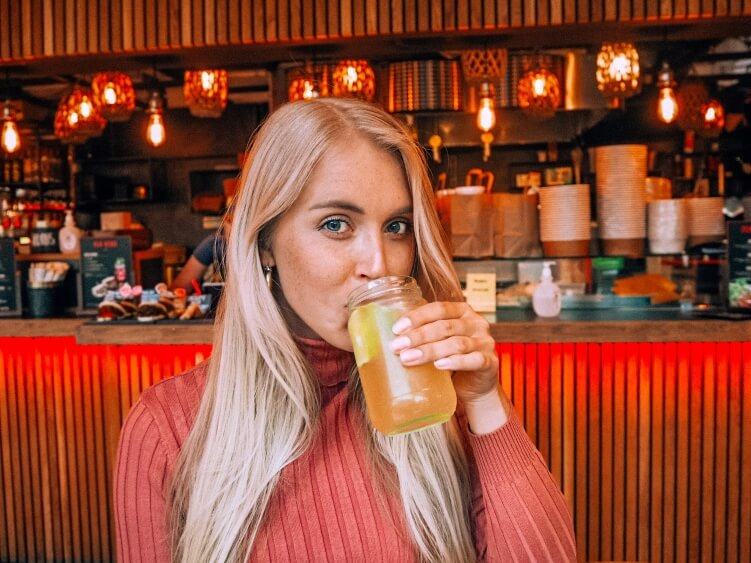a girl sipping homemade ginger lemonade at Tivoli Food Hall, one of the best spots for street food in Copenhagen, Denmark