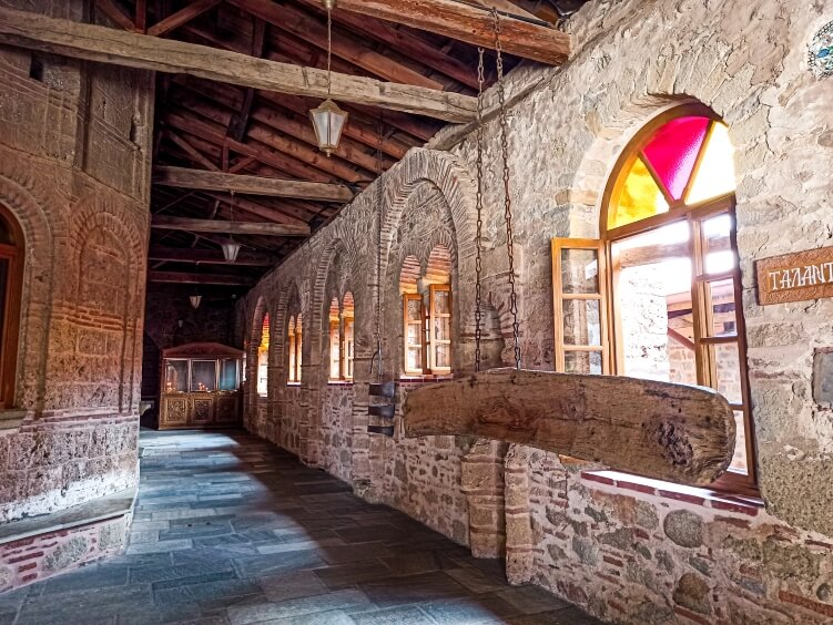Beige brick walls and colorful windows of the Great Meteoron Monastery in Greece; one of the best things to do in Meteora
