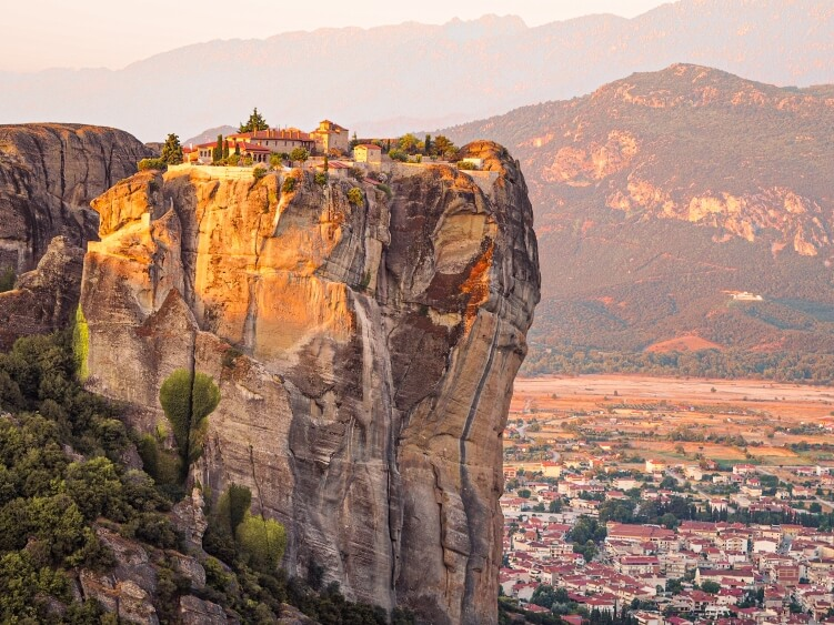 View over The Holy Trinity Monastery perched on top of a steep vertical boulder during sunrise in Meteora near the town of Kalambaka