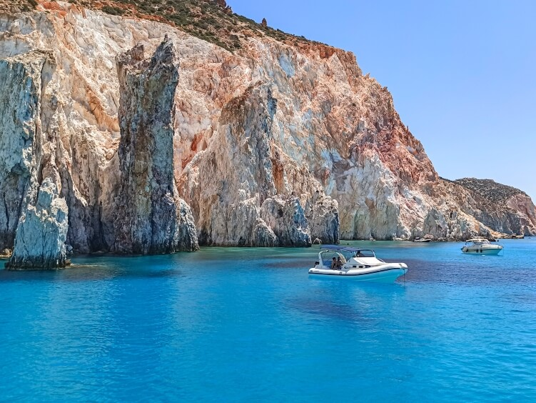 Bright blue waters and orange cliffs of Polyaigos island near Milos, Greece.