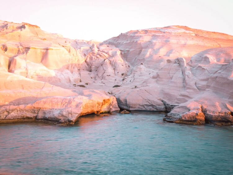 The emerald waters and white lunar landscape of Sarakiniko Beach in Milos at sunrise