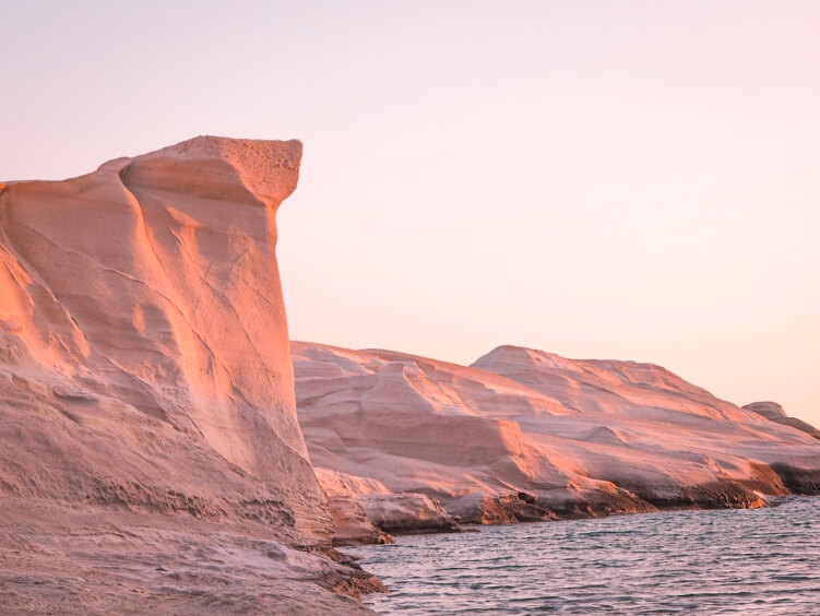 The volcanic cliffs of Sarakiniko beach illuminated by soft pink light during the sunrise.