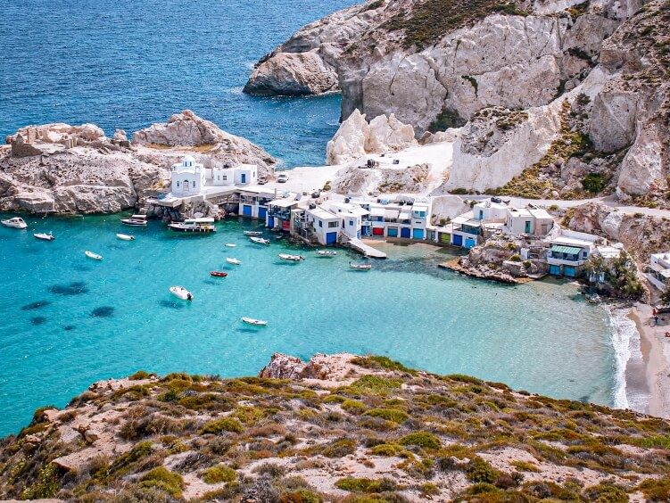 The blue bay and white boat houses of the traditional fishing village Firopotamos on Milos island
