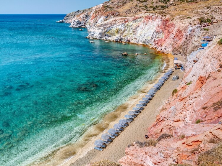 Paleochori beach with its emerald water and surrounding cliffs in shades of red and orange is often named as one of the best beaches in Milos, Greece