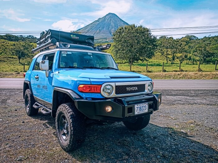 Blue 4x4 car with a rooftop in front of Arenal Volcano