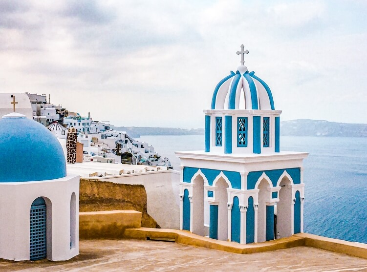 White and blue church dome with a backdrop of Aegean sea, a view on the hike from Fira to Oia in Santorini