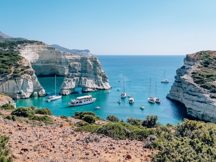 A view of the iconic Kleftiko bay with white rocks, turquoise water and sailing boats on Milos Island, Greece