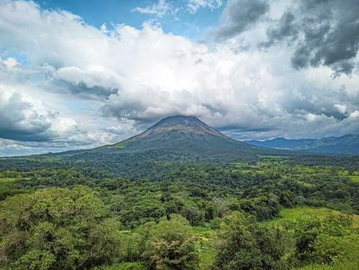 Arenal volcano surrounded by green vegetation and a dramatic cloudy sky in Costa Rica