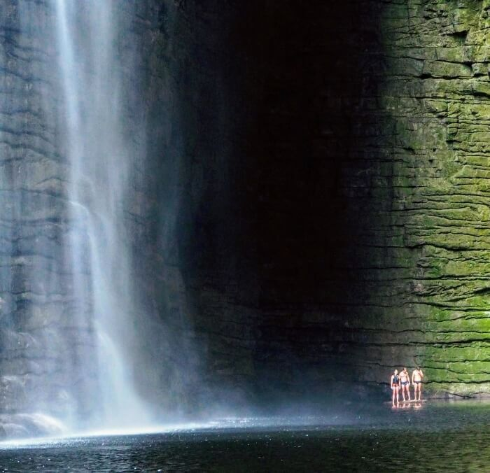 Three people standing next to Cachoeira da Fumacinha waterfall surrounded by a dark canyon