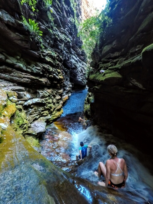 Hikers swimming through a river inside a narrow canyon in Brazil