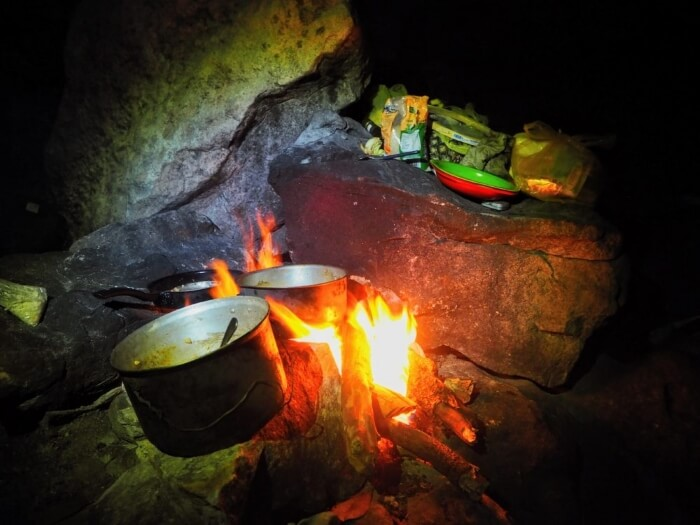 Pots and pans on top of a bonfire in a campsite kitchen at night