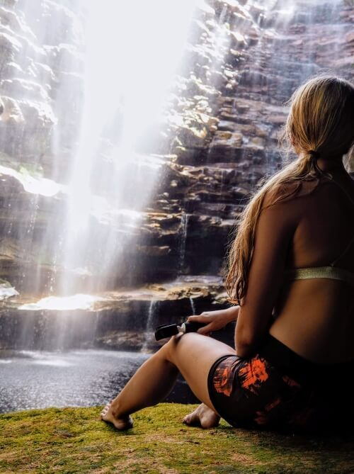 a girl looking at Cachoeira do Mixila waterfall in Chapada Diamantina National Park, one of the best places for hiking in Brazil