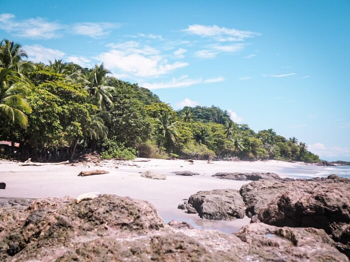 Big rocks on Montezuma beach in Costa Rica on a sunny day, one of the best places in this 10 day Costa Rica itinerary