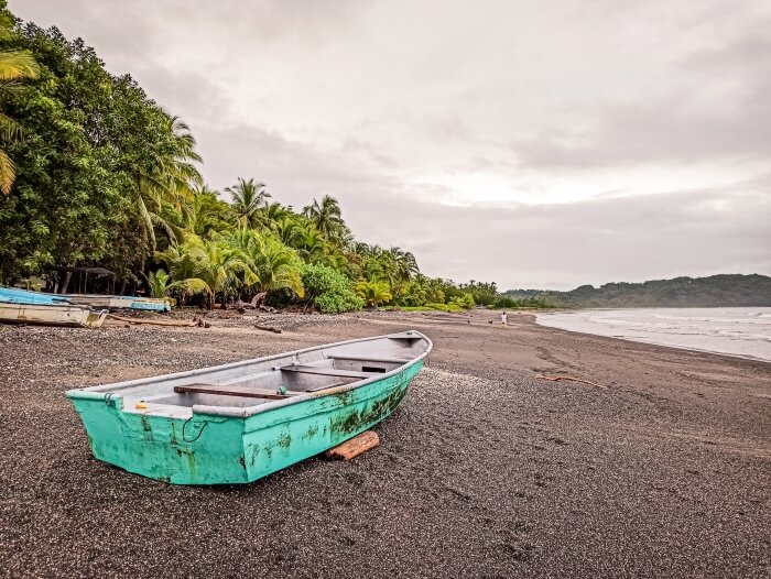 a turquoise fishermen boat on the grey sand of Samara beach on a cloudy day