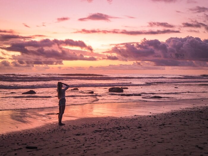 Purple clouds and pink sky during sunset at Santa Teresa beach in Costa Rica
