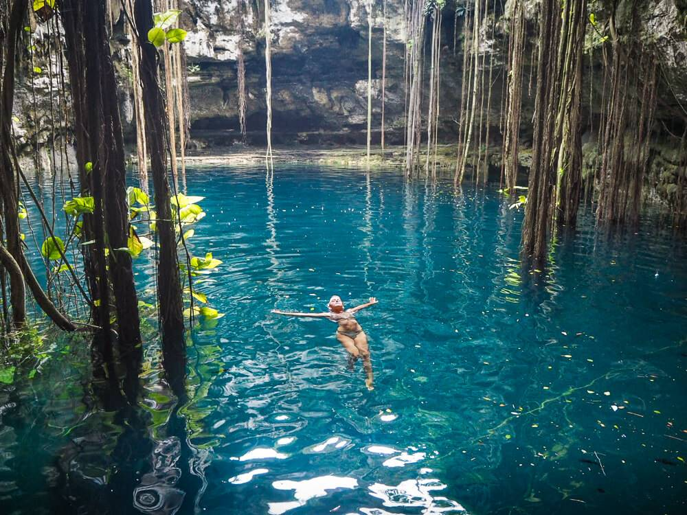a girl swimming in blue water between hanging vines in Cenote Oxman in Mexico, one of the most unique things to do in Valladolid