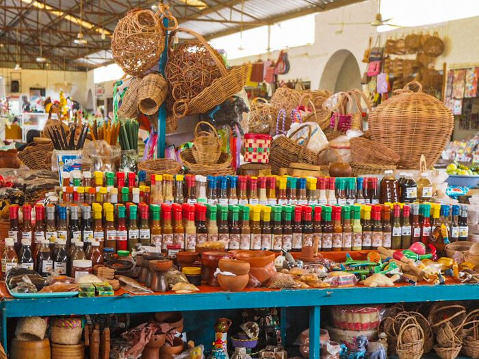 A selection of Mexican salsas in colorful bottles and locally made handicrafts at the Municipal Market of Valladolid