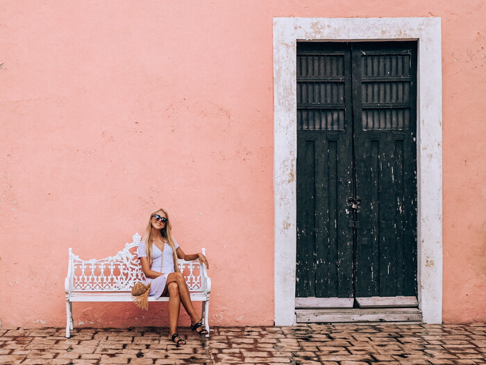 A girl sitting on a white bench in front of a pink wall in Valladolid, Mexico's colorful colonial town