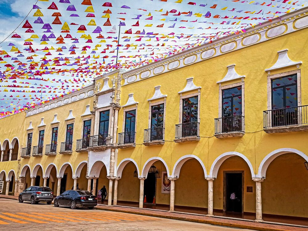 A yellow colonial building decorated with colorful flags in Valladolid, Mexico