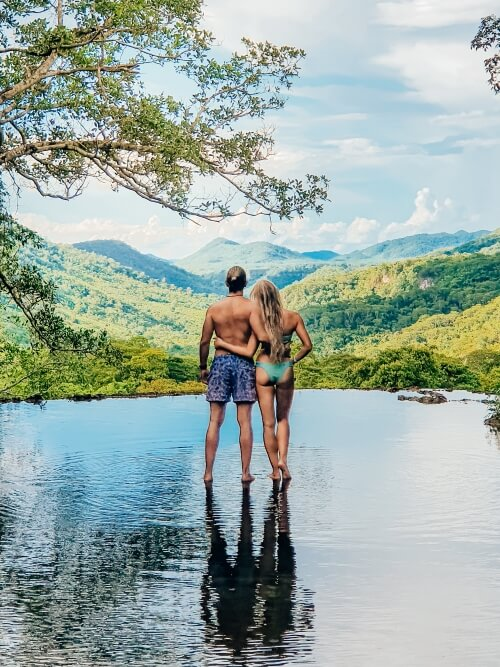 a couple standing in a natural infinity pool during Boca da Onca ecotour in Bonito