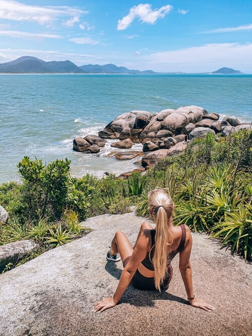 A girl sitting on a rock overlooking the natural pools of Barra da Lagoa in Florianopolis, the last destination of our 10 days in Brazil itinerary