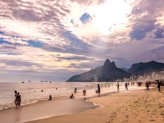 People swimming and sunbathing at the famous Ipanema beach in Rio; in the background there are the Two Brothers mountains.