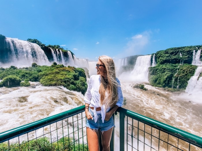 a girl standing in front of the mighty Devil's Throat, a must-see when visiting Iguazu Falls in Brazil