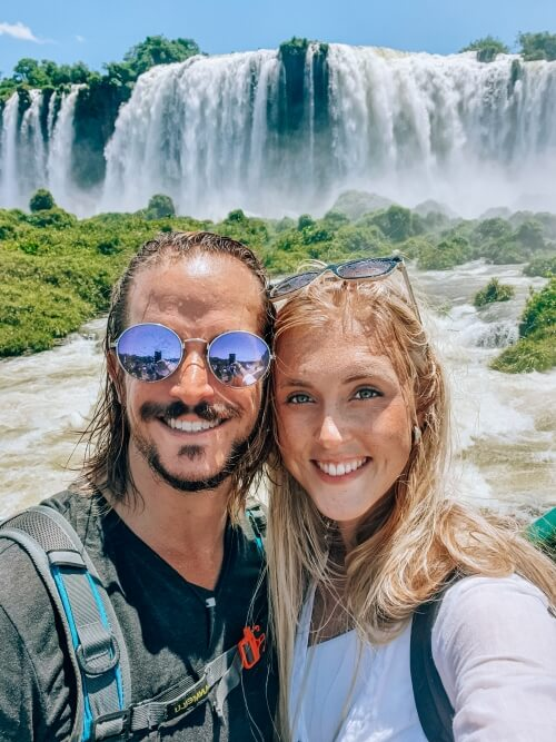 a couple posing in front of Iguacu falls in Brazil