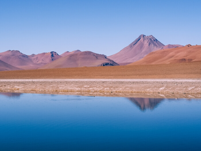 An Altiplanic lake with a backdrop of red volcanoes on the Ruta de los Salares, one of the top Atacama Desert tours for nature lovers.