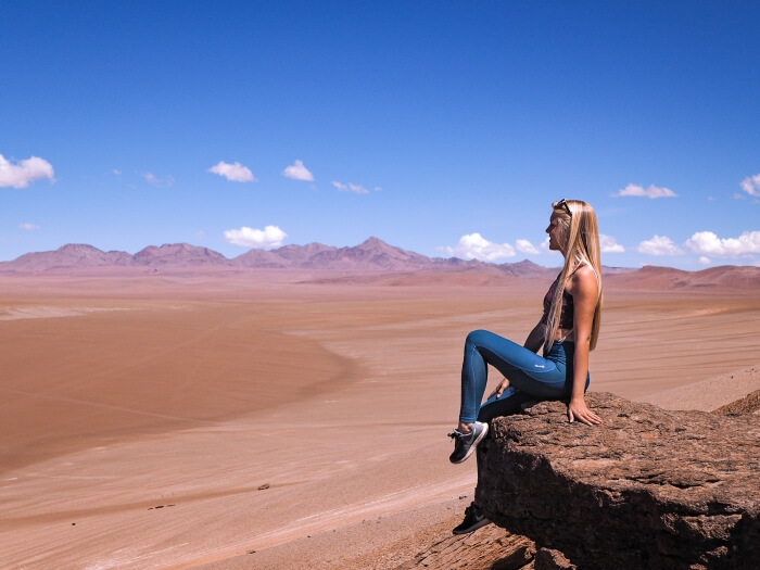 A girl sitting on a rock and admiring the view over rocky landscapes on Ruta de Los Salares in the Atacama Desert