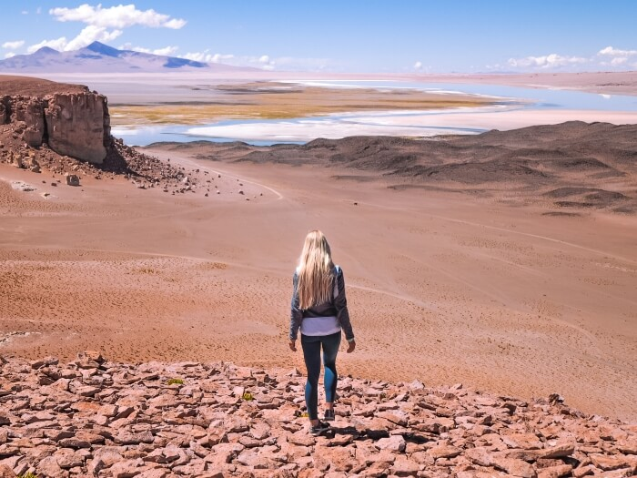 Girl standing on a rocky hill and admiring the view over Salar de Tara salt flat, surely one of the most amazing things to do in Atacama Desert