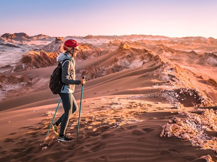 A girl hiking through the Mars-like landscape of Vallecito in Cordillera de la Sal, one of the most unique Atacama Desert tours