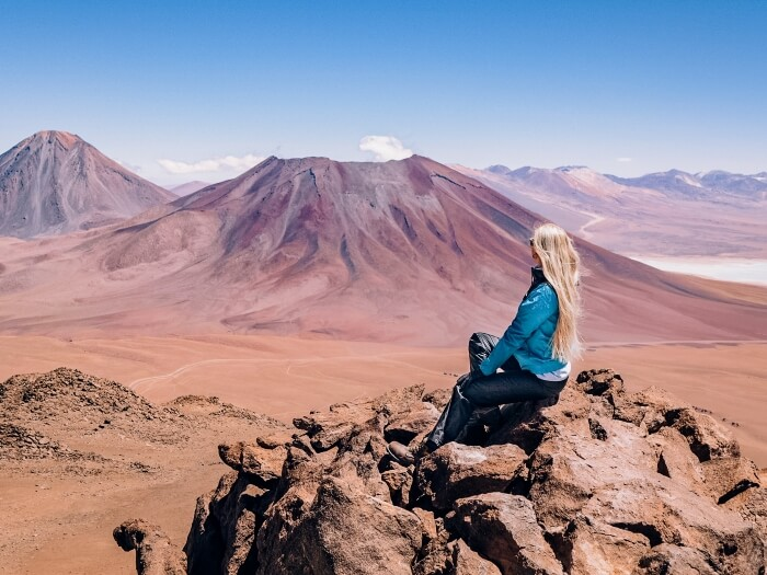 Girl sitting on a rock and admiring a panoramic view after hiking Cerro Toco, one of the best things to do in Atacama Desert