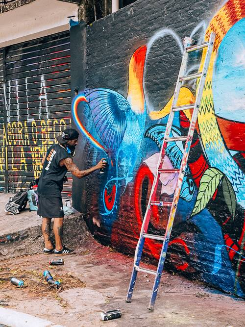 a street artist creating a mural at Beco do Batman