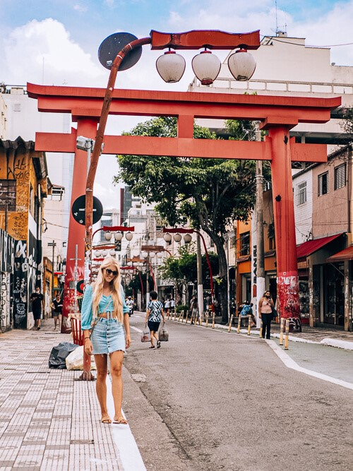 A girl walking in front of a red Torii gate in the Liberdade district of Sao Paulo, which is the residence of the largest Japanese population outside of Japan.