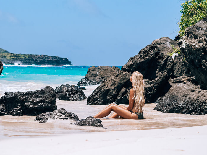 A girl sitting on white sand in Puerto Chino beach, one of the best beaches in  the Galapagos Islands