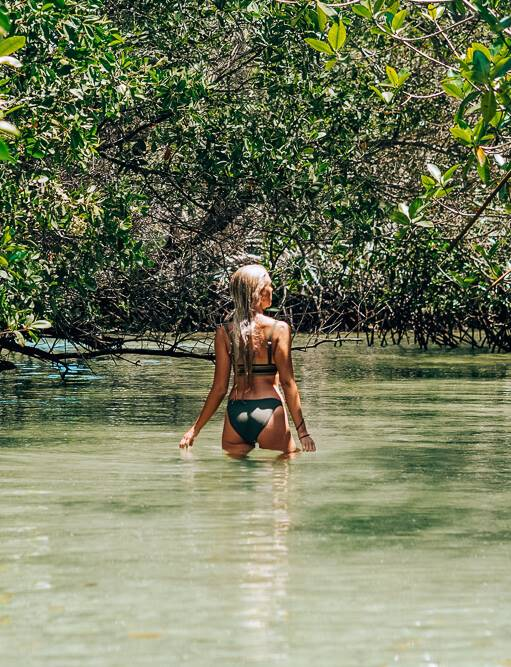 a girl standing in water surrounded by mangroves at El Estero