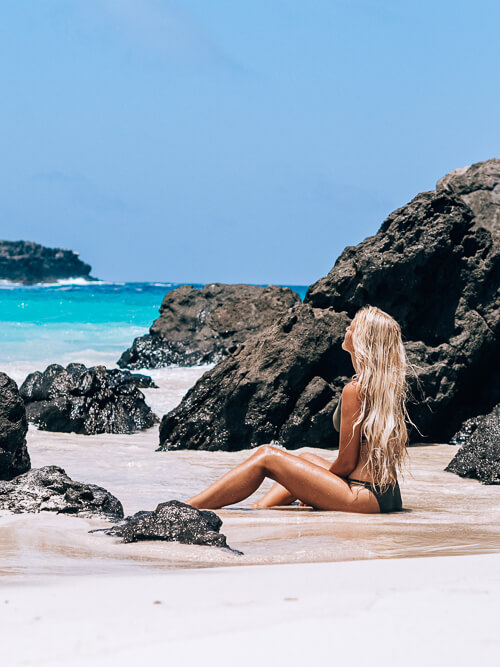 a girl sitting on the white sand of Puerto Chino beach, one of the best Galapagos Islands beaches