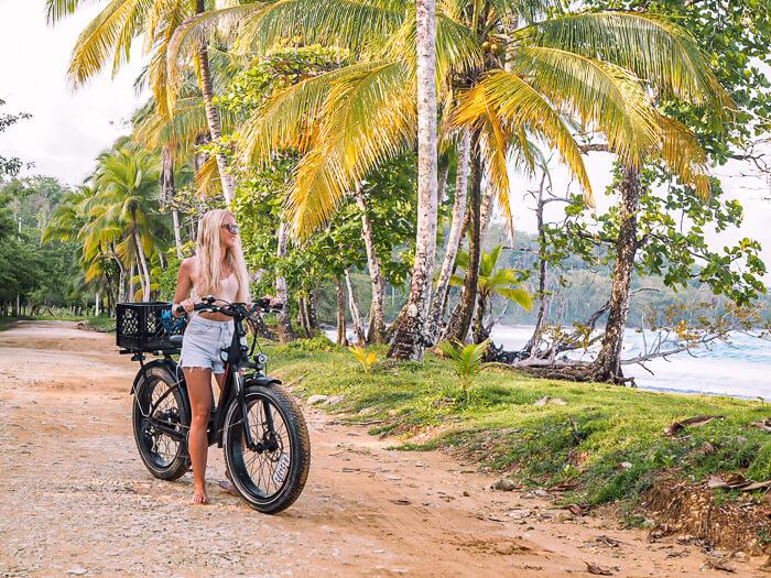 A girl biking on a palm tree-lined coastal dirt road on Isla Colon, Panama
