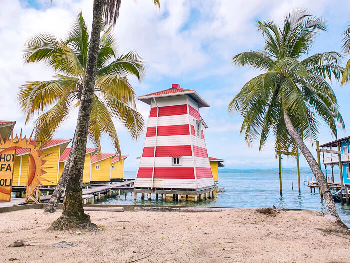 Two palm trees in front of a red and white house built on stilts on Carenero Island in Panama.